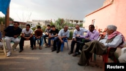 Turkish Kurdish men chat in the village of Doruklu, in the border town of Silopi, near the Turkish-Iraqi border, July 5, 2014.