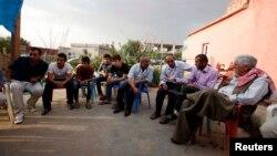 Turkish Kurdish men chat in the village of Doruklu, in the border town of Silopi, near the Turkish-Iraqi border, July 5, 2014.