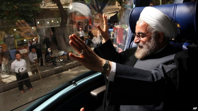 Iranian presidential candidate Hasan Rowhani, a former Iranian nuclear negotiator, waves, from his bus, during his campaign tour to the western city of Sanandaj, Iran, June 10, 2013.