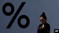 一名中国女子2019年4月4日在北京一家商场耳戴苹果无线耳机正在看苹果手机。