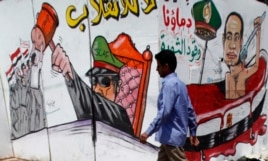 A member of the Muslim Brotherhood and supporter of ousted Egyptian President Mohamed Morsi walks in front of graffiti depicting Abdel Fattah al-Sisi, army commander and defense minister, around Cairo University and Nahdet Misr Square in Giza July 23, 201