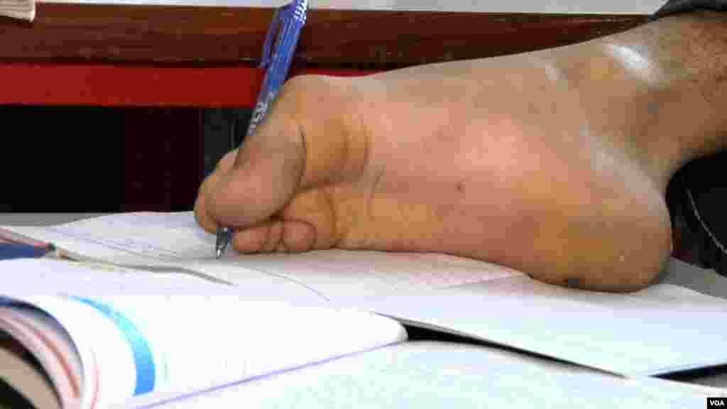 ہاتھوں سے محروم ایک معذور طالب علم پاؤں کی مدد سے اپنے اسکول کا کام کر رہا ہے۔