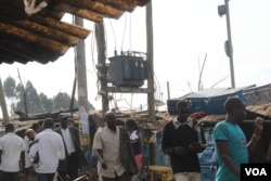 People walk by a large transformer in Kibera, Kenya. Cartels provide electricity to residents at a cost as low as $3 by tapping into such transformers. (R. Ombuor/VOA)