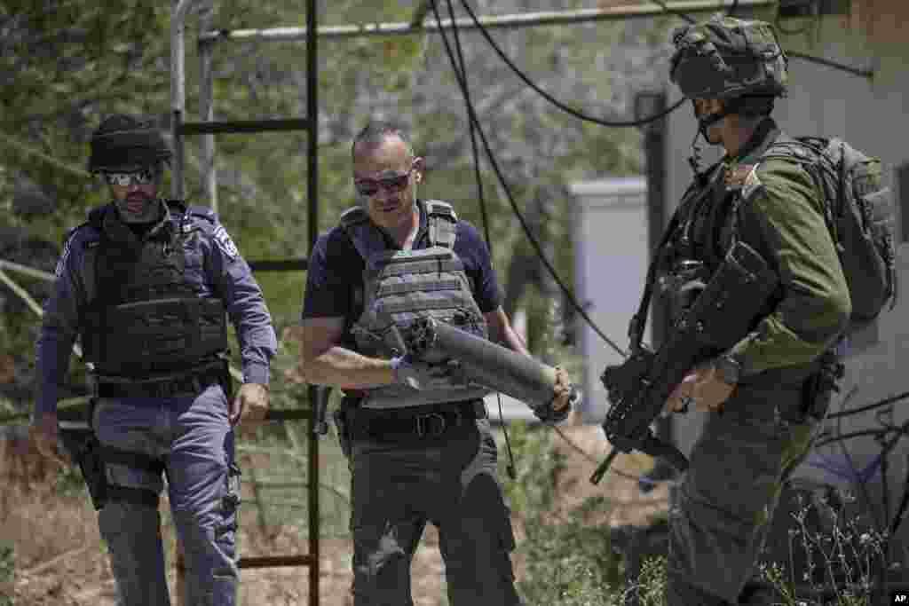 نیروی پلیس اسرائیل در منطقه «موشاو»، تکهای از راکتهای «قسام» پرتاب شده از نوار غزه را در دست دارد. راکت پرانی غزه با حمله هوایی نیروهای اسرائیل روبرو شد.