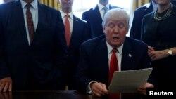 도널드 트럼프 미국 대통령이 24일 백악관 집무실에서 미국 주요 기업 중역들이 지켜보는 가운데 규제개혁 행정명령에 서명했다.