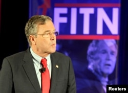 FILE - Former U.S. Republican presidential candidate Jeb Bush stands in front of a photo of former president and brother George W. Bush as he speaks at the New Hampshire GOP's FITN Presidential town hall in Nashua, New Hampshire, Jan. 23, 2016.