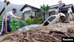 10일 태풍 너구리로 산사태가 발생한 일본 나가노현에서 한 남성이 흙더미를 치우고 있다.