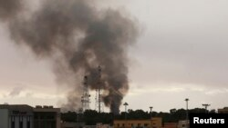 Black smoke billows above areas where pro-government forces and fighters from the Shura Council of Libyan Revolutionaries are battling in Benghazi, Dec. 11, 2014.