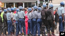 FILE: Zimbabwean police officers keep an eye on opposition party supporters as they prepare to march during a protest aimed at President Robert Mugabe in Harare, Zimbabwe, March, 14, 2016.