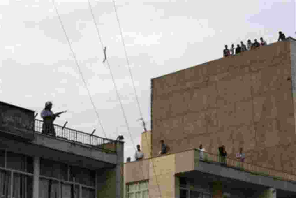 A member of a pro-government militia, left, stands guard on a rooftop of their base as demonstrators approach, near a rally supporting leading opposition presidential candidate Mir Hossein Mousavi in Tehran, Iran, Monday, June 15, 2009. Shots were fired