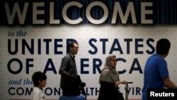 FILE - International passengers arrive at Washington Dulles International Airport.