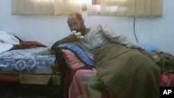반군 측 휴대폰에 찍혀 19일 경 온라인에 공개된 가다피의 차남 사이프 알 이슬람의 모습으로 오른쪽 손가락에 부상을 입고 침대에 누운 채 억류돼 있다.