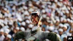 Para demonstran di Dhaka membawa patung pemimpin Myanmar Aung San Suu Kyi sebelum membakarnya dalam aksi pro Rohingya hari Jumat (25/11).