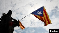 An Estelada (Catalan separatist flag) waves overhead during a protest one day after the banned independence referendum in Barcelona, Spain, Oct. 2, 2017.