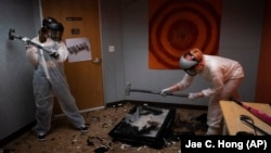 To release stress, Piper Mape, 17, right, and sister, Berkley, 15, use sledgehammers to destroy a TV in a rage room at Smash Rx in Westlake Village, California, February 5, 2021. (AP Photo/Jae C. Hong)