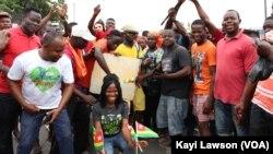 """Manifestants posant avec une pancarte sur laquelle est écrit """"retour à la constitution de 92, vote de la diaspora, 50 ans ça suffit!"""", à Lomé, le 6 septembre 2017. (VOA/Kayi Lawson)"""