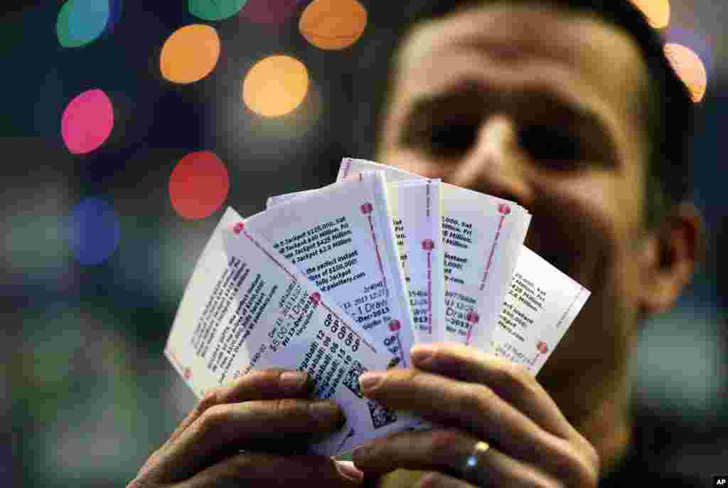 Chad Cuneo displays Mega Millions lottery tickets he purchased at a newsstand in Philadelphia, Pennsylvania. Superstition didn't deter players hoping that Friday the 13th will bring them good luck in the  game.