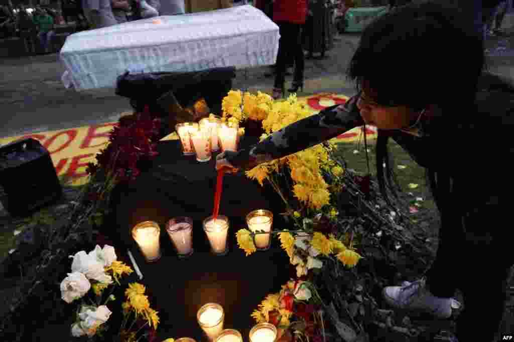 Niña enciende una vela en memoria de las víctimas del COVID-19 durante una protesta contra el Bicentenario de la Independencia de Guatemala.
