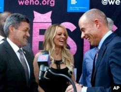 FILE - West Hollywood Mayor John Duran, left, adult film star Stormy Daniels and attorney Michael Avenatti attend a ceremony for Daniels at which she received a ceremonial key to the city, May 23, 2018, in West Hollywood, Calif.