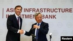 중국을 방문한 빌 모르노 캐나다 재무장관(왼쪽)이 31일 베이징에서 기자회견을 열고 아시아인프라투자은행(AIIB) 가입을 발표한 후, 진리췬 AIIB 총재와 악수하고 있다.