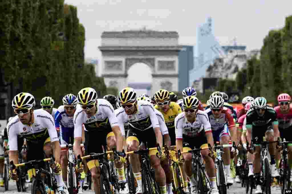 (L-R) Spain's Jonathan Castroviejo, Great Britain's Christopher Froome, Netherlands' Wout Poels, Great Britain's Geraint Thomas, wearing the overall leader's yellow jersey, and Poland's Michal Kwiatkowski ride in the pack in front of the Arc de triomphe monument during the 21st and last stage of the 105th edition of the Tour de France cycling race between Houilles and Paris Champs-Elysees.