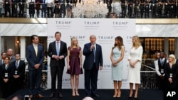 FILE - Then-candidate Donald Trump, accompanied by his family, speaks during the grand opening of the Trump International Hotel-Old Post Office, Washington, Oct. 26, 2016.