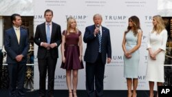 FILE - Then-candidate Donald Trump, accompanied by his family, speaks during the grand opening of the Trump International Hotel-Old Post Office, Washington, Oct. 26, 2016. Experts on government ethics are warning President-elect Trump that he'll never shake suspicions of a clash between his private interests and the public good if he doesn't sell off his vast holdings.