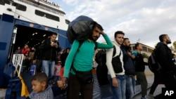 难民们携带着自己的财物,一同乘坐比雷埃夫斯雅典港口的莱斯沃斯岛的渡轮(2015年9月30日)。