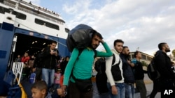 A man carries his belongings as other migrants and refugees arrive on a ferry from the Greek island of Lesbos at the Athens' port of Piraeus, Sept. 30, 2015.