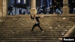 Një palestinez hedh gurë ndaj policisë izraelite gjatë përplasjeve në xhaminë Al-Aqsa