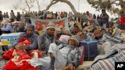 Bangladeshi migrant workers rest while they wait to return home at a refugees camp near the Libyan and Tunisian border crossing of Ras Jdir after fleeing unrest in Libya, March 5, 2011