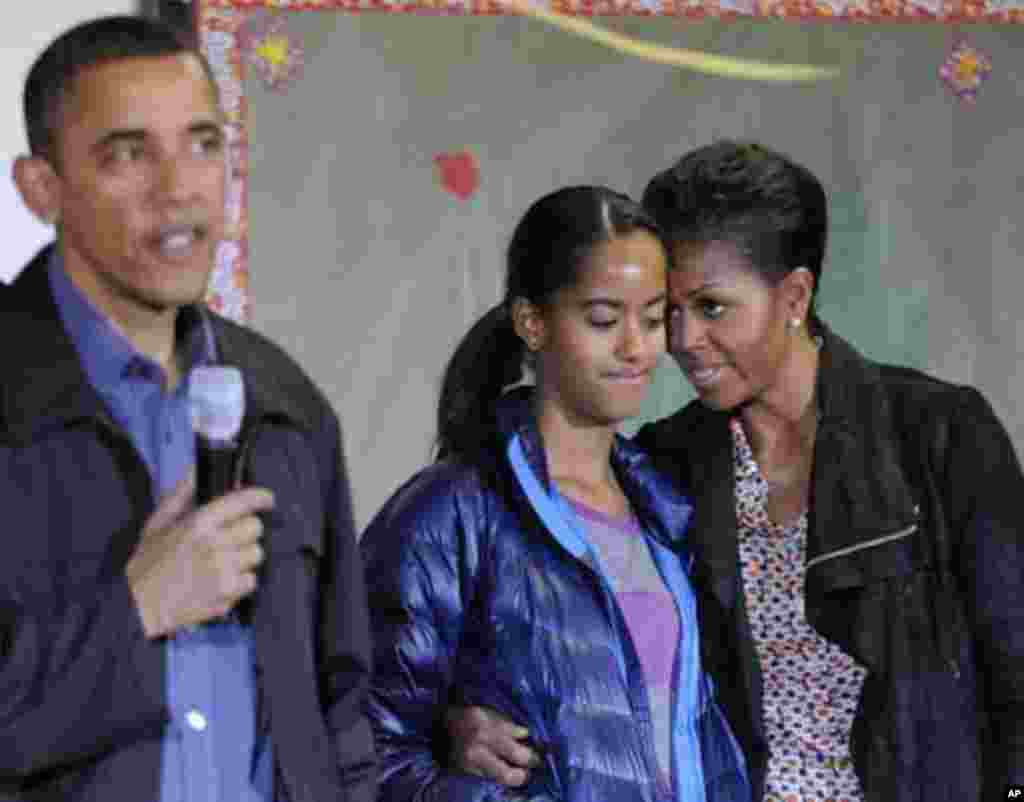 First lady Michelle Obama (R) stands with her daughter Malia (2nd R) as U.S. President Barack Obama (L) delivers remarks during a day of service to honor Martin Luther King, Jr, at the Browne Education Campus school in Washington, January 16, 2012. REUTER