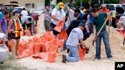 کارکنان شهرداری و داوطلبان کیسه های شن را برای حفاظت خانه ها آماده می کنند.