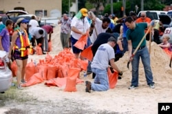 FILE - Orlando city employees and volunteers fill sandbags for residents as they prepare for Hurricane Irma in Orlando, Florida, Sept. 8, 2017. Lines of vehicles stretched for miles and many waited several hours to get the sandbags.