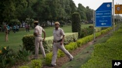 FILE - Indian policemen secure the area outside the Pakistan High Commission as Kashmiri separatist leaders arrive for talks with the Pakistani high commissioner in New Delhi, India.