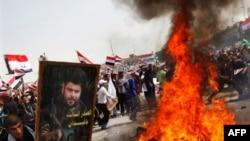 Những người ủng hộ Giáo sĩ Moqtada al-Sadr đốt cờ Mỹ trong một cuộc tuần hành đánh dấu 8 năm quân đội Mỹ tiến vào thủ đô Baghdad của Iraq, ngày 9 tháng 4, 2011