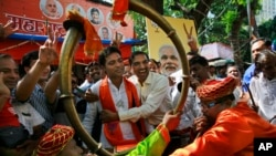 Pendukung Partai Bharatiya Janata (BJP) merayakan hasil awal yang menunjukkan partai tersebut menang dalam pemilihan di Mumbai, India, 19 Oktober 2014.