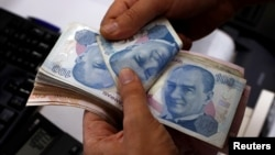 A money changer counts Turkish lira notes at a currency exchange office in Istanbul, Aug. 2, 2018.