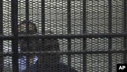 Habib el-Adly (au premier plan) derrière les barreaux, durant son récent procès pour corruption
