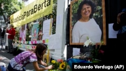 A woman places flowers on an altar set up in honor of Berta Caceres during a demonstration outside Honduras' embassy in Mexico City.