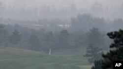 2013年10月6日在北京郊外举行的华彬女子高尔夫精英赛上,选手在雾霭弥漫中挥杆比赛