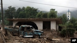 Mexico Tropical Weather: A pickup truck lays destroyed next to a house damaged by a mudslide in Xaltepec, on the mountainous north of Puebla state, Mexico, Sunday, Aug. 7, 2016.