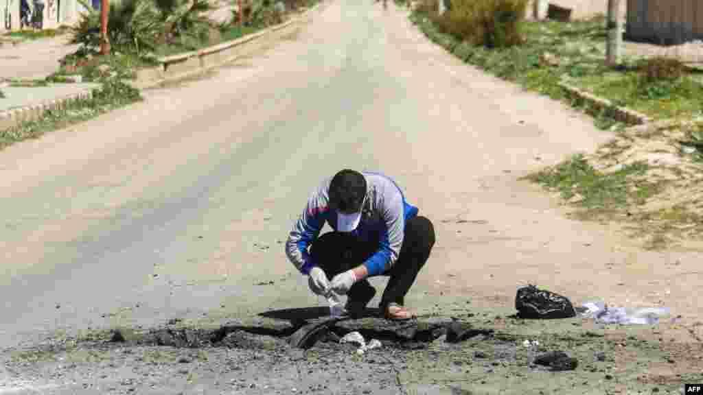 Un Syrien recueille des preuves sur le lieu de l'attaque chimique à Khan Sheikhun, le 5 avril 2017.