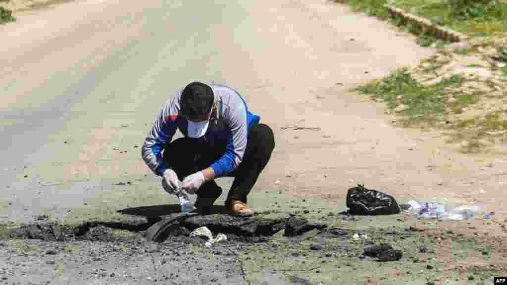 Un hombre sirio recoge muestras del sitio donde se cree se realizó el ataque en Khan Sheikhun, en la provincia de Idlib, Siria el 4 de abril de 2017.