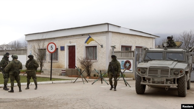 Armed men, believed to be Russian servicemen, stand guard outside a Ukrainian military unit in the village of Perevalnoye outside Simferopol, March 11, 2014.