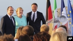 FILE - Italian Premier Matteo Renzi, right, French President Francois Hollande, left, and German Chancellor Angela Merkel stand on the deck of an Italian aircraft carrier off the coast of Italy, Aug. 22, 2016. The leaders of Italy, France and Germany are watching the U.S. election closely.