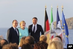 FILE - Italian Premier Matteo Renzi, right, French President Francois Hollande, left, and German Chancellor Angela Merkel stand on the deck of an Italian aircraft carrier off of Italy, Aug. 22, 2016. The leaders of Italy, France and Germany are watching t
