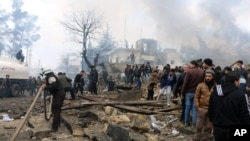 Rescue workers attend to the wreckage left by a bomb that went off in a busy market in the rebel-held Syrian town of Azaz along the Turkish border, Jan. 7, 2017.