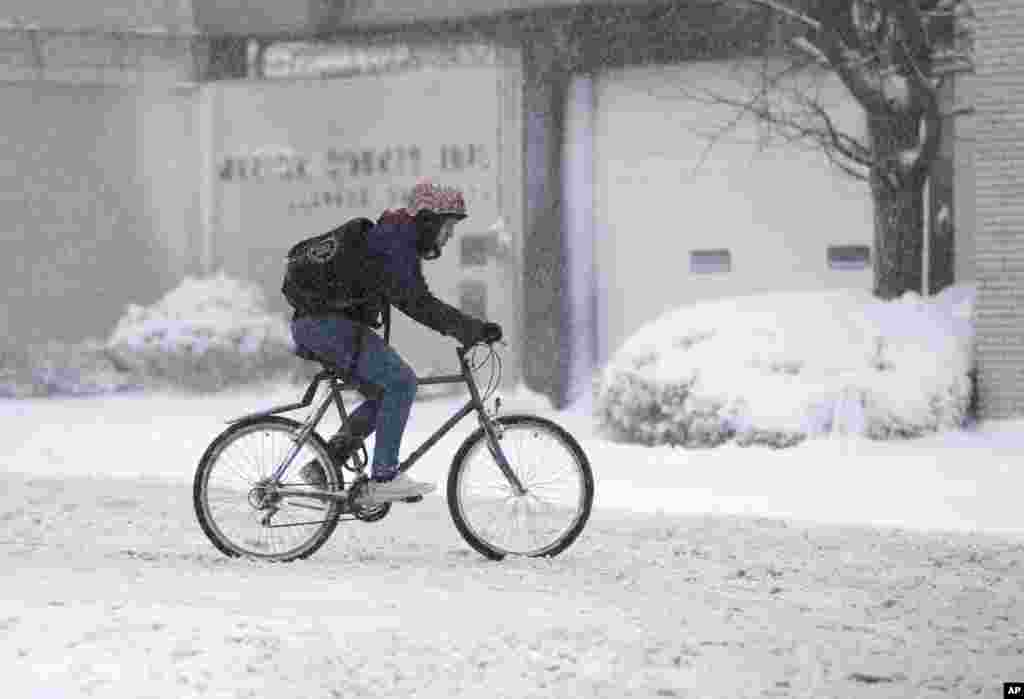A man rides his bicycle through the streets as he makes a delivery in Indianapolis, Indiana, December 26, 2012.