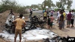 也门人在围观一辆自杀汽车炸弹杀手为刺杀亚丁市长而被炸毁的汽车。(2016年7月15日)